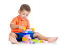Cheerful kid boy playing with construction set over white back Stock Photo