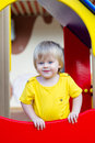 Cheerful kid on the playground positive little boy in bright yellow t shirt Stock Image