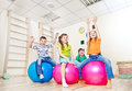 Cheerful kids with their hands up on large gym balls Stock Photography