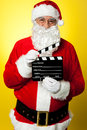 Cheerful Kris Kringle posing with clapperboard Royalty Free Stock Image