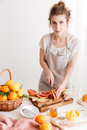 Cheerful lady standing near table with a lot of citruses Royalty Free Stock Photo