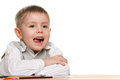 Cheerful little boy at the desk Royalty Free Stock Photography