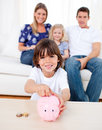 Cheerful little boy inserting coin in a piggybank Stock Image