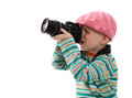 Cheerful little boy photographer holds camera wears beret red scarf striped sweater beige pants Royalty Free Stock Images