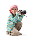 Cheerful little boy is a photographer he holds the camera he wears a beret red scarf striped sweater and beige pants Stock Images