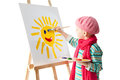 Cheerful little boy standing at the easel young artist holds in his hands the palette with paints he paints the sun Royalty Free Stock Photography