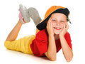 A cheerful little child with funny cap is lying Stock Photo