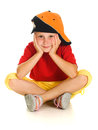 A cheerful little child with funny cap is sitting Royalty Free Stock Image