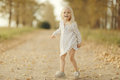 Cheerful little girl at autumn road