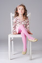 Cheerful little girl with curly long hair sitting on the white chair wearing pink clothes making faces Stock Image