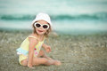 Cheerful little girl with Down syndrome with glasses resting on the sea coast