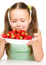 Cheerful little girl is smelling strawberries isolated over white Stock Photography