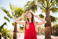 Cheerful lovely young woman in red dress and hat walking and talking on mobile phone on summer resort and palms background. Royalty Free Stock Photo
