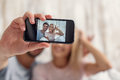 Cheerful lovers photographing themselves on phone Royalty Free Stock Photo