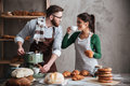 Cheerful loving couple bakers drinking coffee. Looking aside. Royalty Free Stock Photo