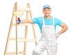 Cheerful male decorator holding a paint roller in white jumpsuit and blue shirt and leaning on wooden ladder isolated on Stock Image