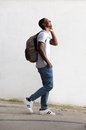 Cheerful male student walking and talking on cell phone Royalty Free Stock Photo