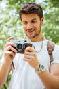 Cheerful man with backpack taking pictures using vintage camera outdoors Royalty Free Stock Photo