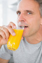 Cheerful man drinking orange juice in kitchen looking at camera Stock Photography