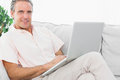 Cheerful man on his couch using laptop looking at camera Royalty Free Stock Photo