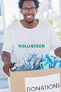Cheerful man holding donation box full of clothes Stock Images