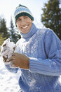 Cheerful man holding snowball portrait of a happy young in winter Stock Photo