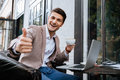 Cheerful man with laptop showing thumbs up in outdoor cafe Royalty Free Stock Photo