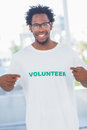 Cheerful man pointing to his volunteer tshirt in a modern office Stock Image
