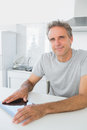 Cheerful man using tablet pc in kitchen looking at camera Royalty Free Stock Image