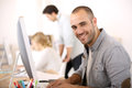 Cheerful man working on computer guy sitting in front of desktop Royalty Free Stock Images