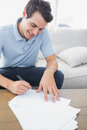 Cheerful man writing on a paper in the living room Stock Photos