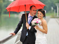 Cheerful married couple standing near a river under umbrella Royalty Free Stock Image