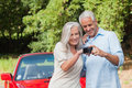 Cheerful mature couple looking at pictures on their camera while leaning against cabriolet Royalty Free Stock Image