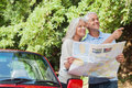 Cheerful mature couple reading map looking for direction by their cabriolet Royalty Free Stock Photos