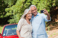 Cheerful mature couple taking pictures of themselves leaning against their cabriolet Stock Photography