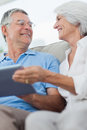 Cheerful mature couple using a digital tablet sitting on couch Royalty Free Stock Photos