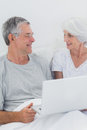 Cheerful mature couple using a laptop in bed Royalty Free Stock Images