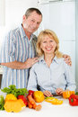 Cheerful mature man and woman smiling together portrait of men women at a kitchen Royalty Free Stock Photos