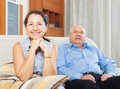 Cheerful mature woman against elderly man women men in home interior Stock Photos