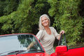 Cheerful mature woman getting off her convertible after long ride Stock Images