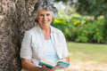 Cheerful mature woman holding book sitting on tree trunk smiling at camera Stock Photos