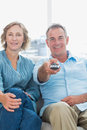 Cheerful middle aged couple sitting on the couch watching tv at home in living room Royalty Free Stock Photo