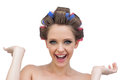 Cheerful model posing with hair curlers young on white background Royalty Free Stock Image