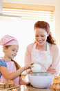 Cheerful mother and daughter preparing dough Royalty Free Stock Images