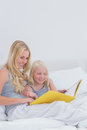 Cheerful mother and daughter reading a story together in bed Royalty Free Stock Photography