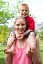 Cheerful mother giving her son piggy-back ride Stock Photos
