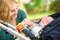 Cheerful mother with her baby giving toy for teething Stock Photography
