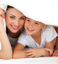 Cheerful mother and her girl playing on a bed Stock Photography