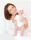 Cheerful mother with little baby portrait of attractive brunette carry cute girl in hands at home happy motherhood young family Royalty Free Stock Images