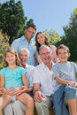 Cheerful multi generation family sitting on a bench in park looking at camera Stock Images